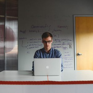 Man sitting at laptop with notes behind him on the wall