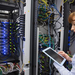 Woman looking at cabling in a server rack